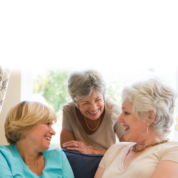 Trio of older women smiling and talking