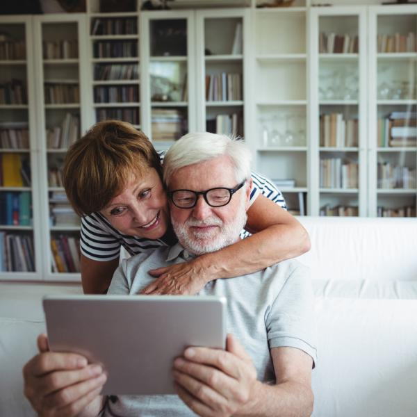 Older couple on couch looking at tablet