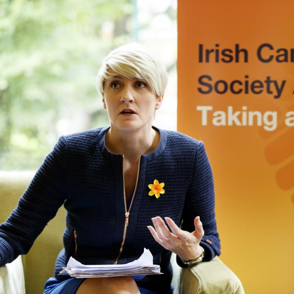 Averil Power sitting in front of a sign: Irish Cancer Society Advocacy - Taking action