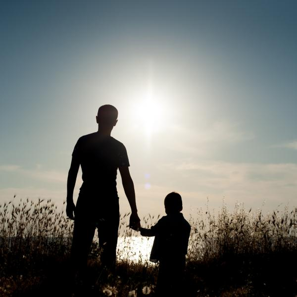 Father and child standing against a sunset