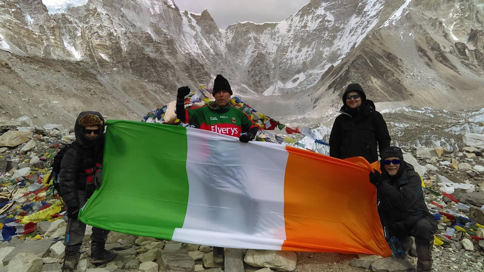 Trekkers holding an Irish flag on a mountain