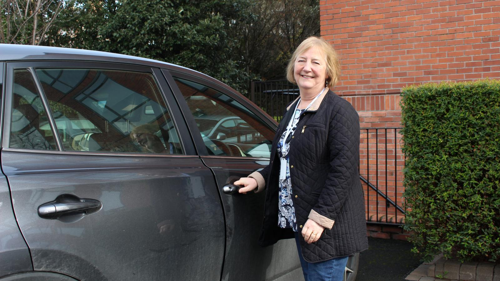 Volunteer driver standing by her car