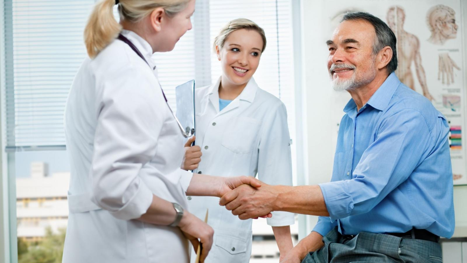 Doctor and nurse greeting patient