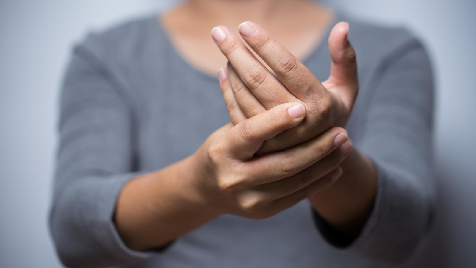 Woman experiencing pain and numbness in her hand