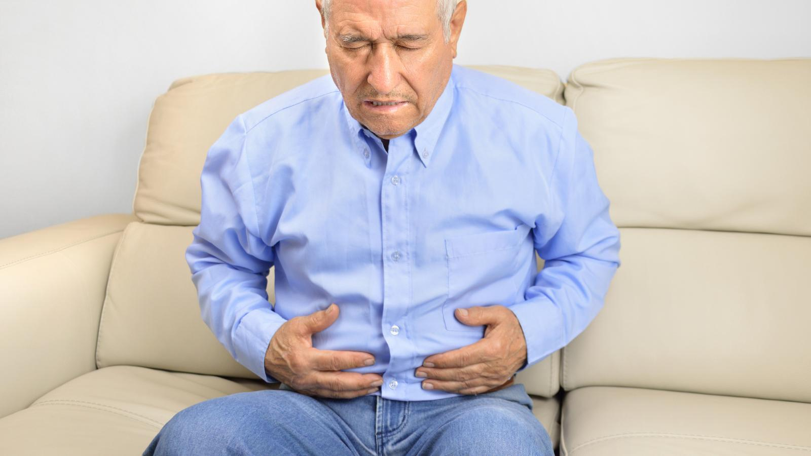 Older man holding his stomach in pain
