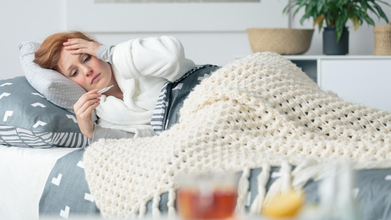 Woman laying in bed feeling sick
