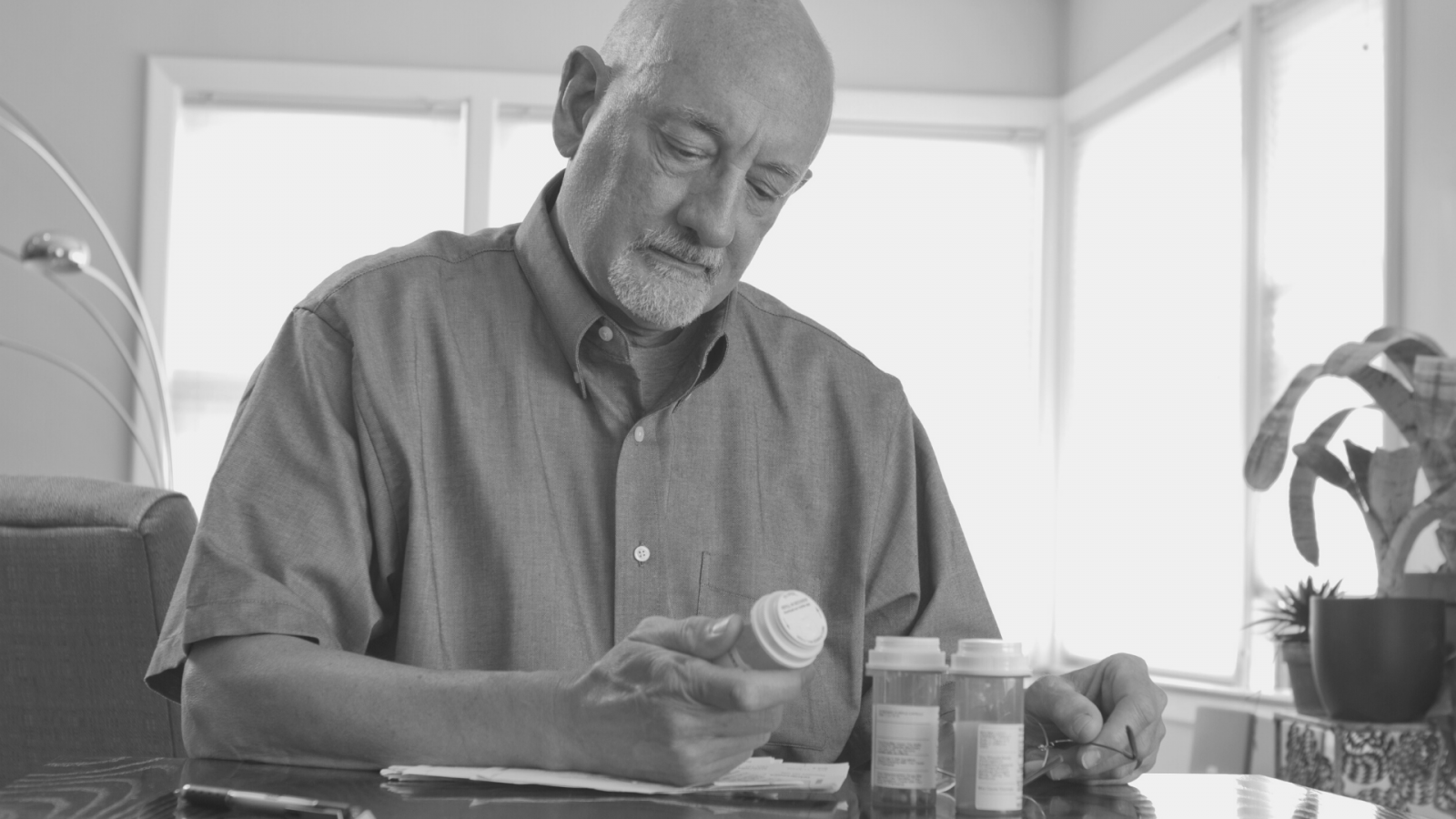 older man looking at medication