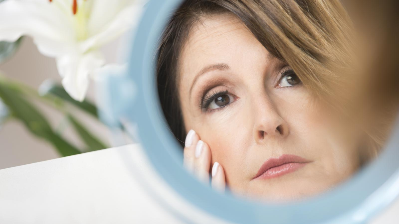 Worried woman looking at her skin in the mirror