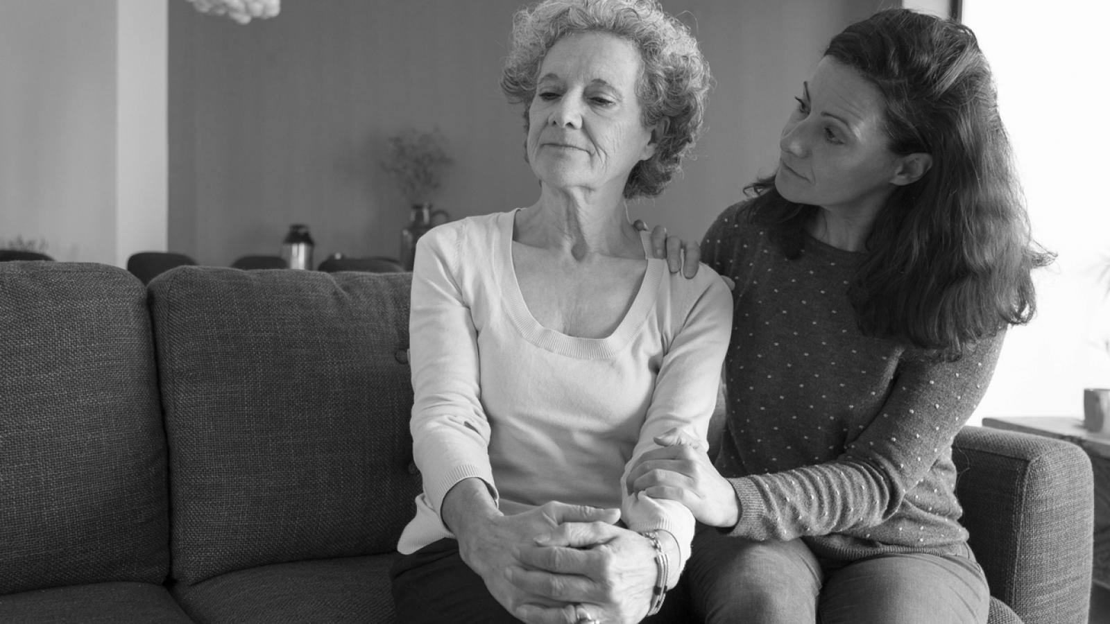 Younger woman consoling older woman on couch