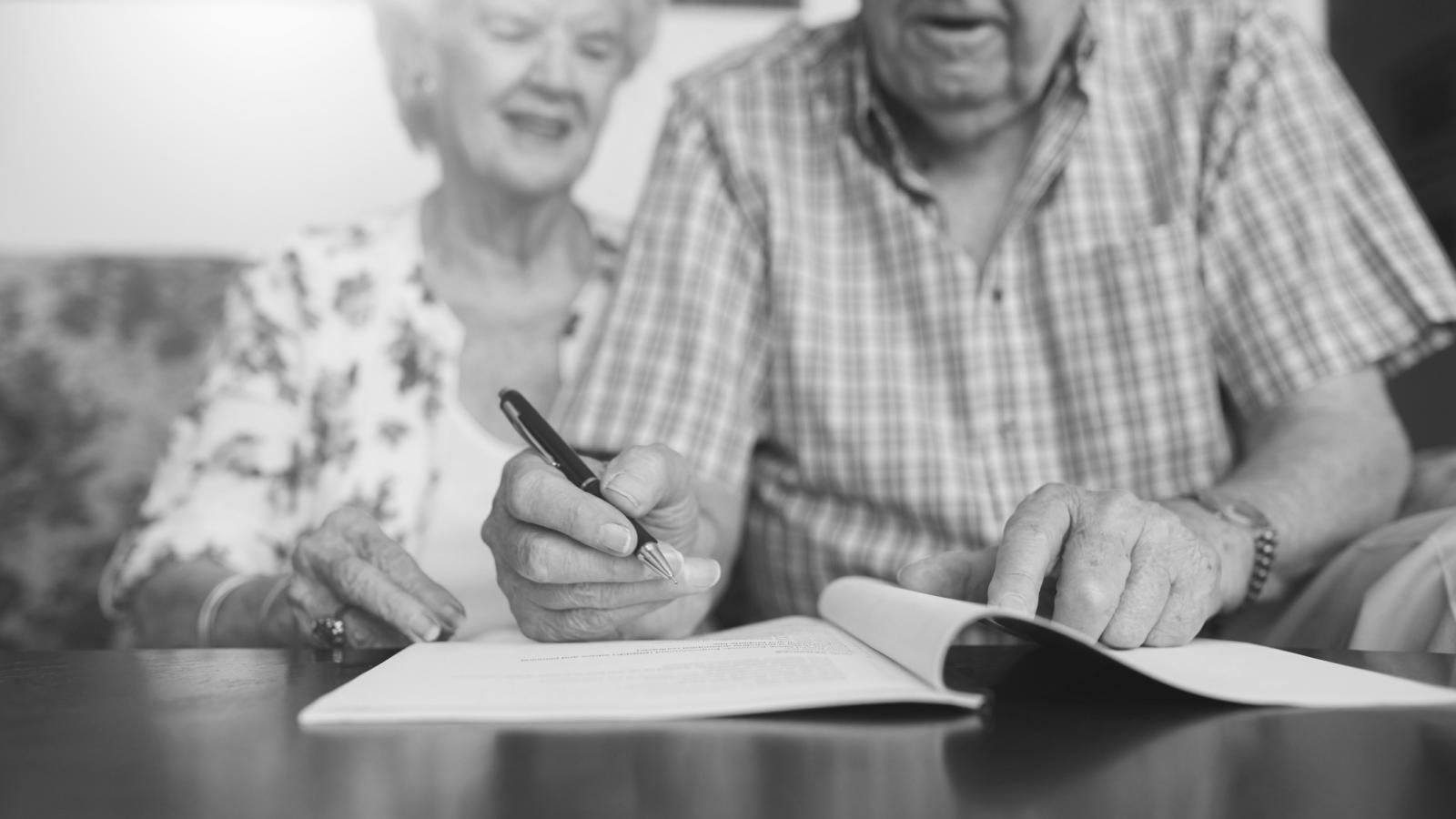 Older couple signing documents