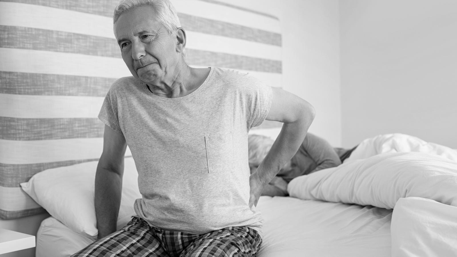 Older man in pain sitting in bed