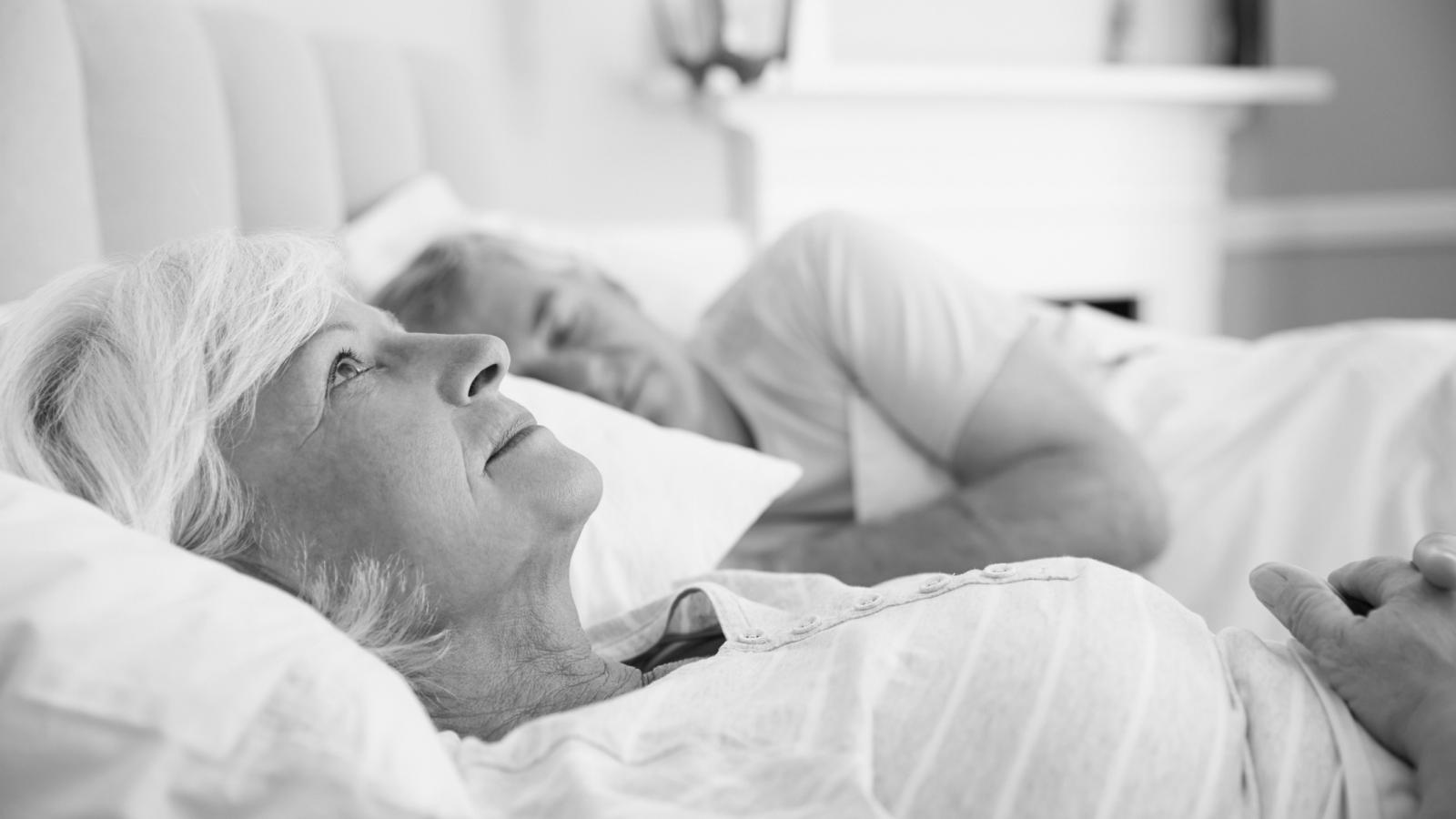 Older couple laying awake in bed